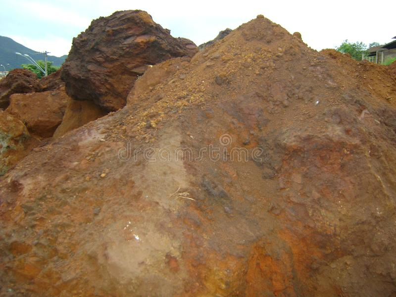 Excavation on land with iron ore. Heap of iron ore land, on land being excavated for construction in Barrão de Cocais, Minas Gerais. The area is all of ore stock photography