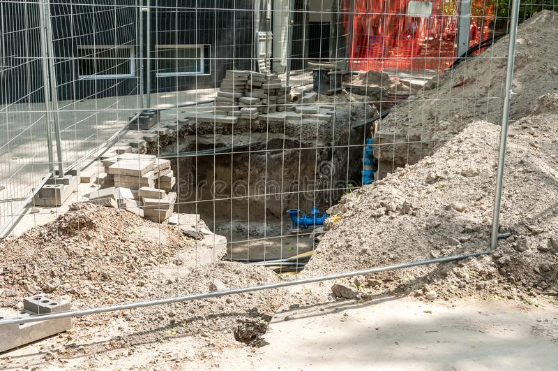 Excavation site for new drinking water pipe valve surrounded with protective metal fence or barrier on the sidewalk with pavement royalty free stock photos