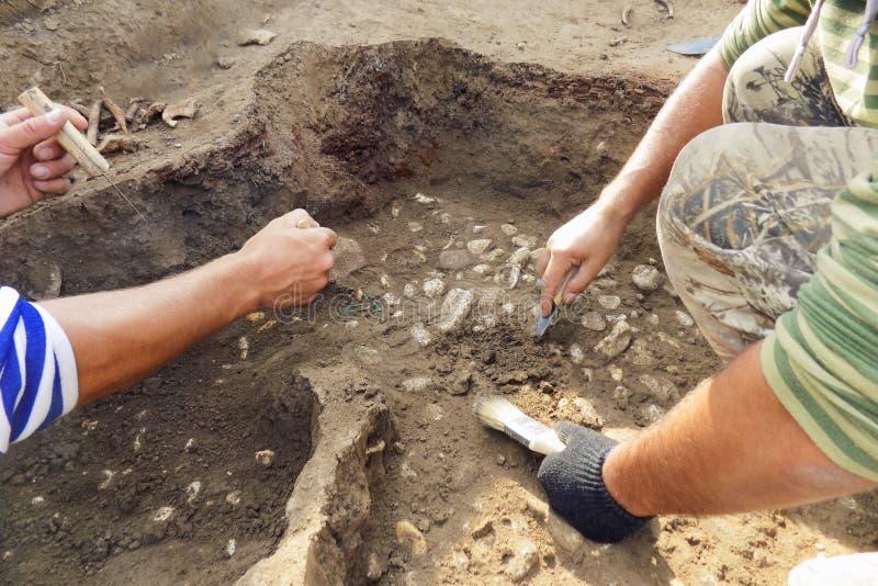 Excavations archéologiques l'archéologue avec des outils conduit la recherche sur l'enterrement humain, squelette, crâne photo stock