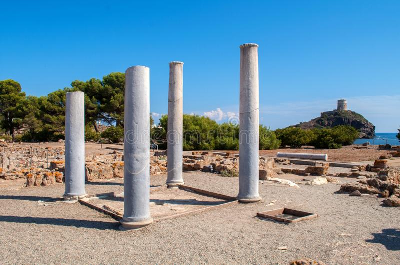 Excavations in city Nora Sardinia, Italy. Excavations and remains of old columns with a tower in the background near the town of Nora on the island of Sardinia royalty free stock photo