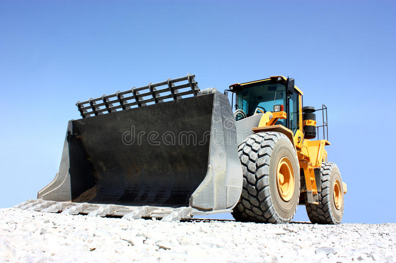 A excavator. A yellow excavator isolated on a clear blue sky background stock photos