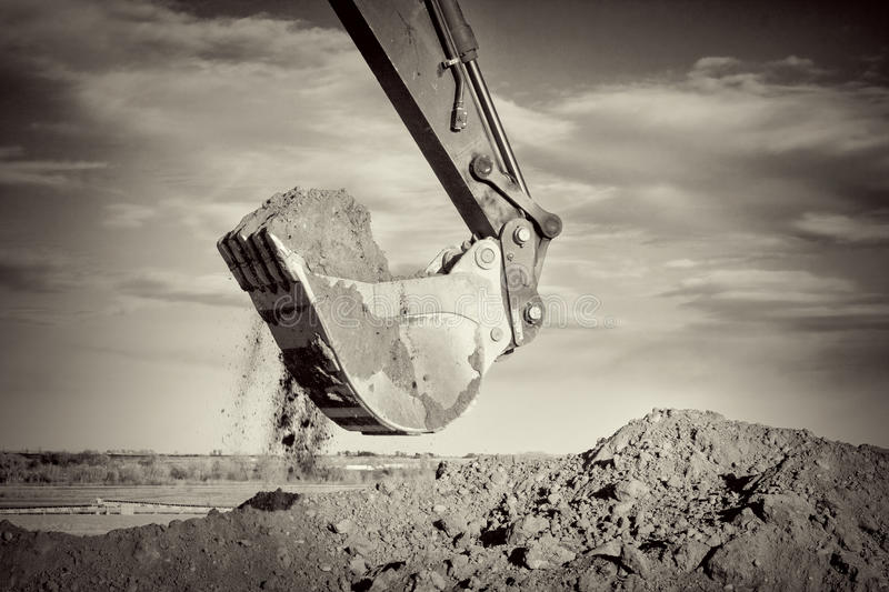 Excavator arm and scoop digging dirt at construction site royalty free stock photos