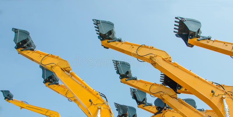 Excavator bucket with blue sky. Excavator bucket on the end of a yellow hydraulic arm of a digging machine stock photos