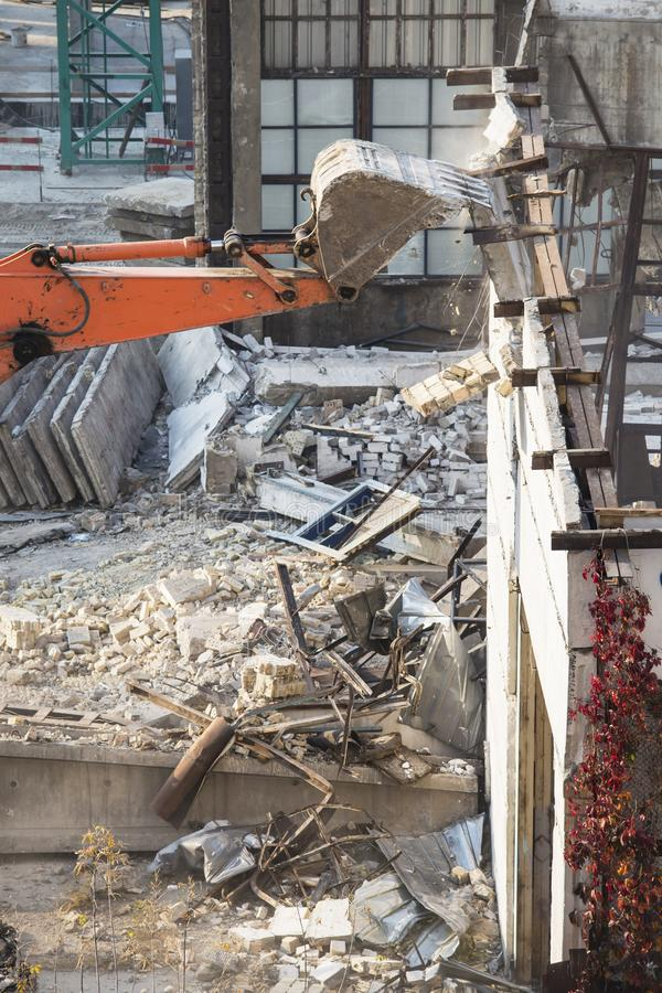 Excavator bucket destroys an old building on site stock image