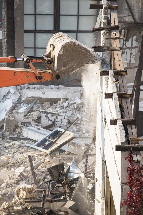 Excavator bucket destroys an old building on site stock photo