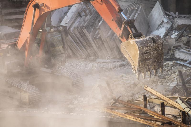 Excavator bucket destroys an old building on site stock photography