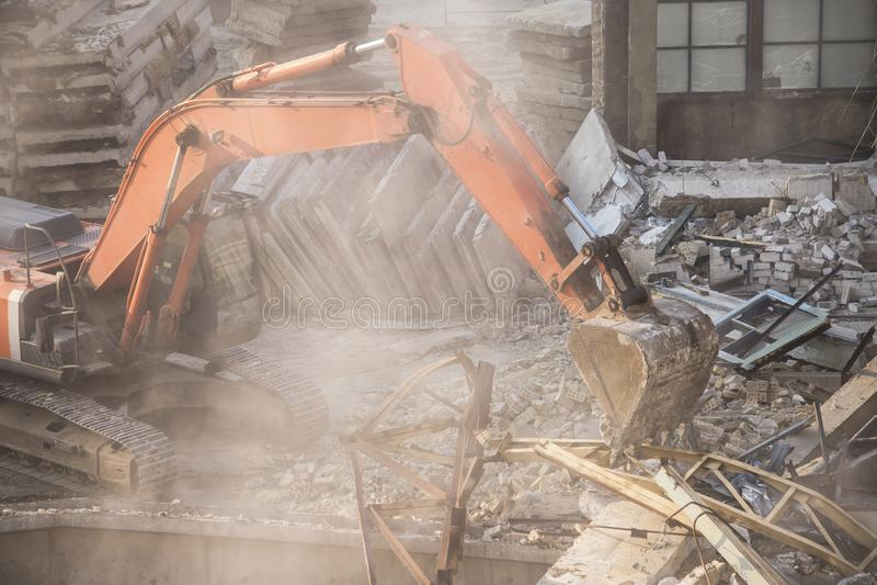 Excavator bucket destroys an old building on site stock photos