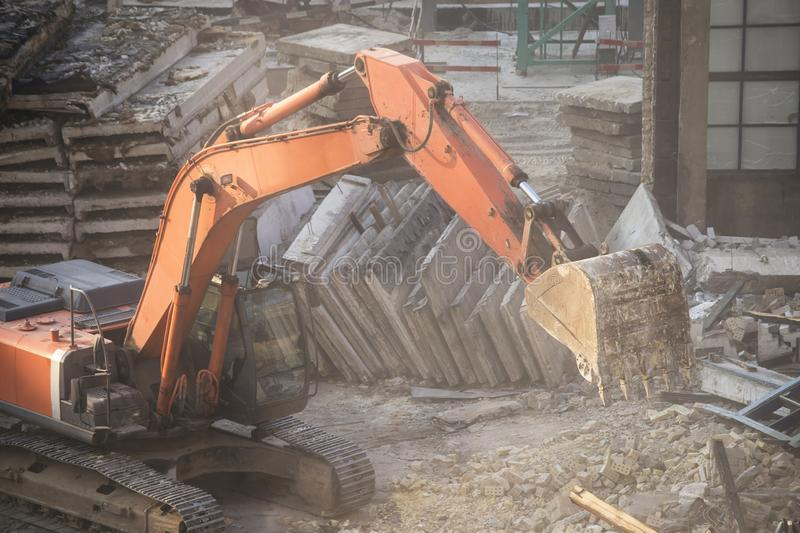 Excavator bucket destroys an old building on site royalty free stock photos