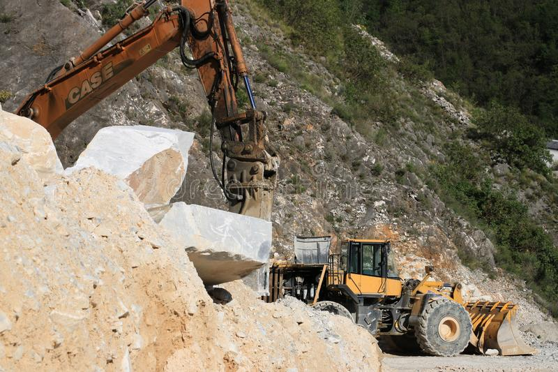 An excavator and a bulldozer in a Carrara marble quarry. A large royalty free stock photos
