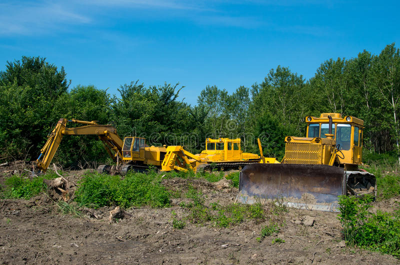 Excavator and bulldozer clearing forest land. stock photography