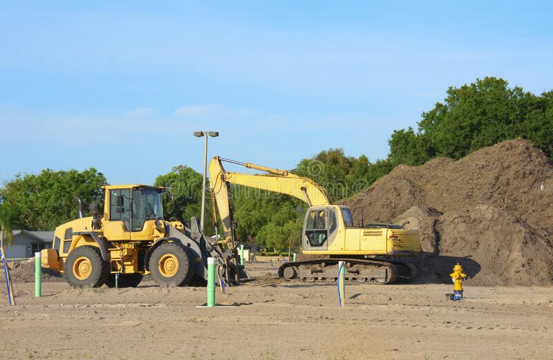 Excavator and bulldozer at a construction site with a large pile of dirt stock images