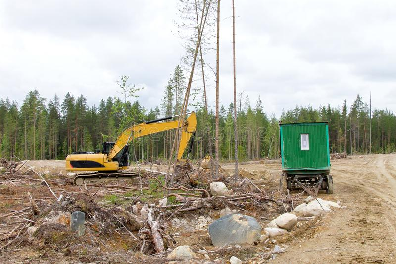 Excavator and cabins for forestry workers on a forest felling plot royalty free stock photos