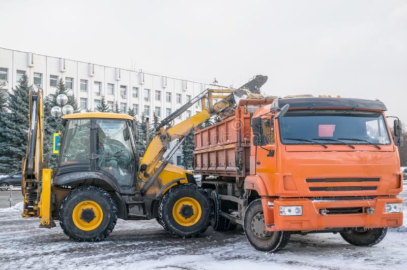Excavator cleaned the snow and loads it into the dump truck.  royalty free stock image