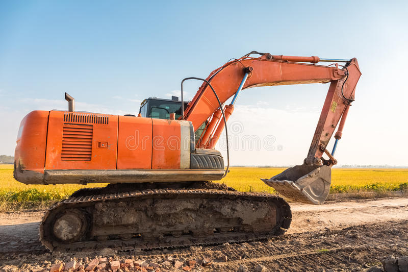 Excavator on the country road. With autumn field scenery royalty free stock photo