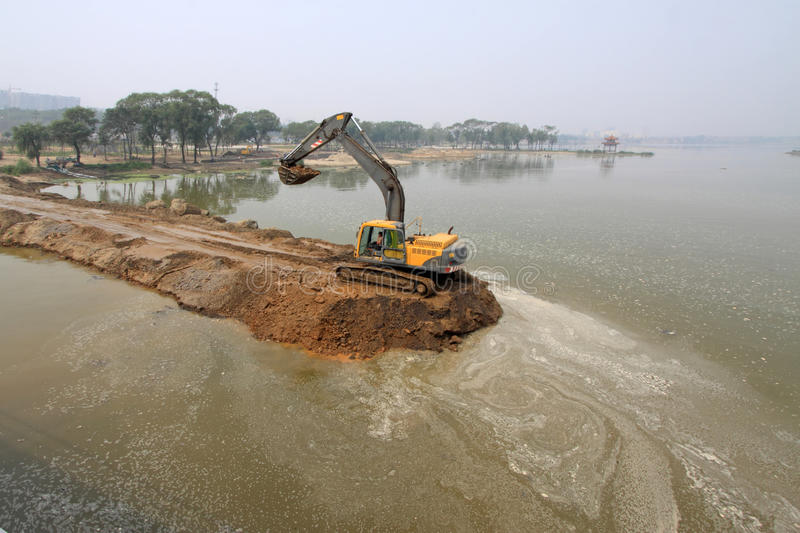 Excavator in a dam construction site. In china royalty free stock photo