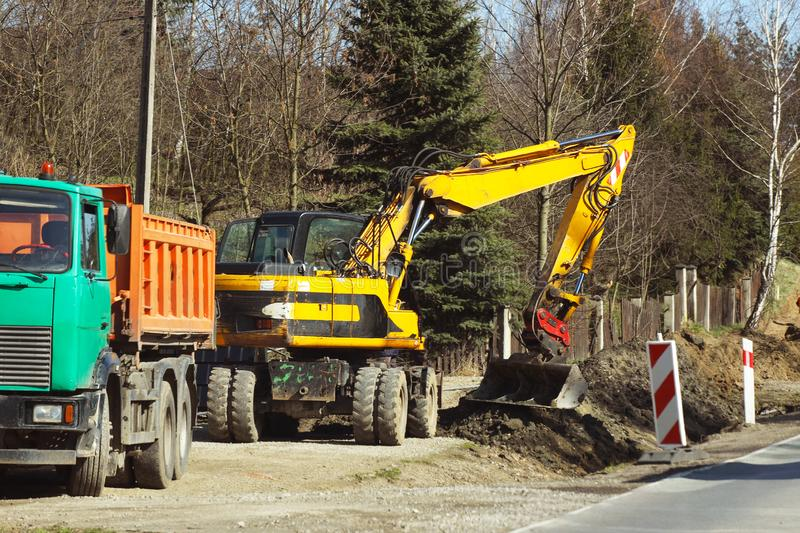 Excavator delivers construction waste to the truck. Cleaning the site for new construction. Construction works. Landscape design. And layout of the city. Heavy stock image