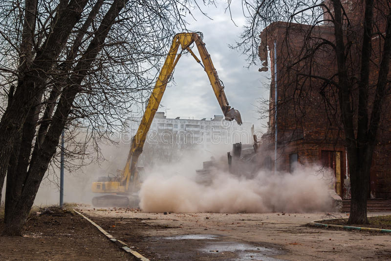 Excavator demolishes old school building royalty free stock image