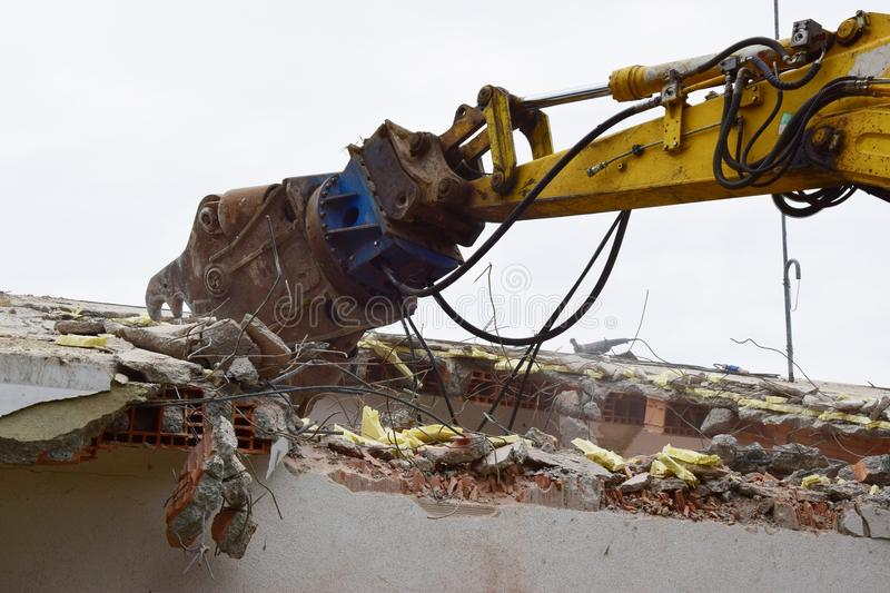 Excavator for demolishing. Excavator in action for demolishing buildings, a close up, front loader royalty free stock photos