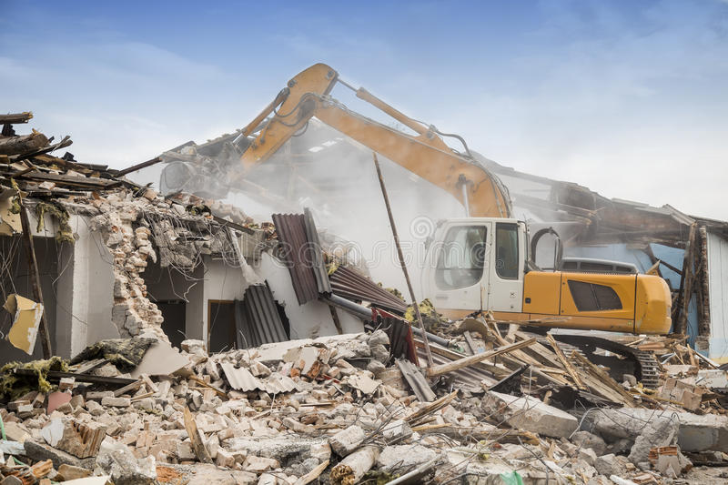 Excavator demolishing barracks. For new construction project. Made with shallow depth of field stock photo