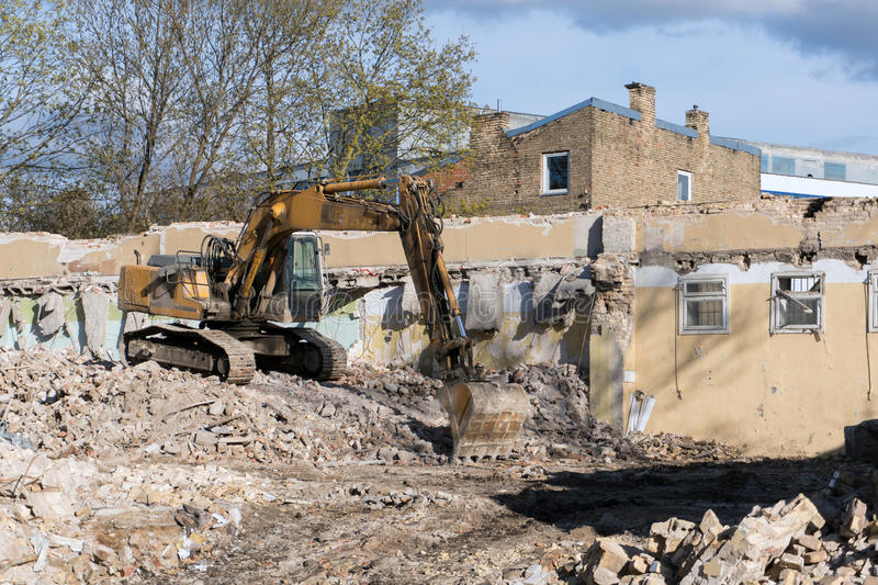 Excavator demolishing building. Excavator in rubble and debris demolishing old building with blue sky on a sunny day royalty free stock image
