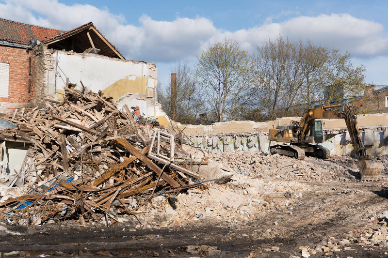 Excavator demolishing building. Excavator in rubble and debris demolishing old building with blue sky on a sunny day stock image