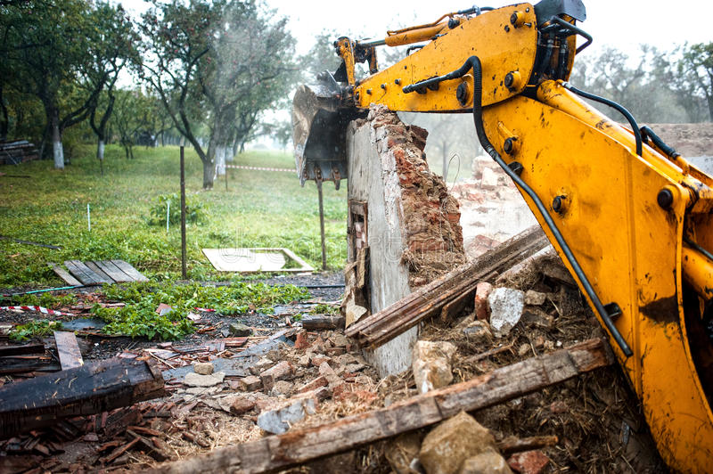 Excavator demolishing a concrete wall. Bulldozer loading demolition debris and concrete waste for recycling at construction site royalty free stock images