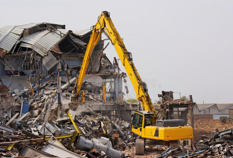 Excavator Demolishing Factory. Yellow excavator demolishing a factory stock photography