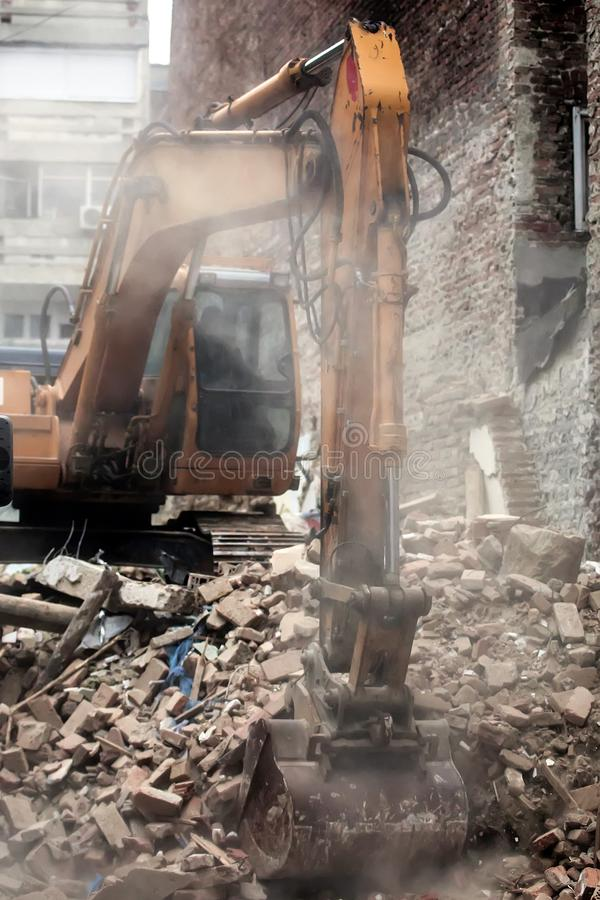 Excavator demolishing a house. Excavator demolishing a brick house on a cloudy day stock images