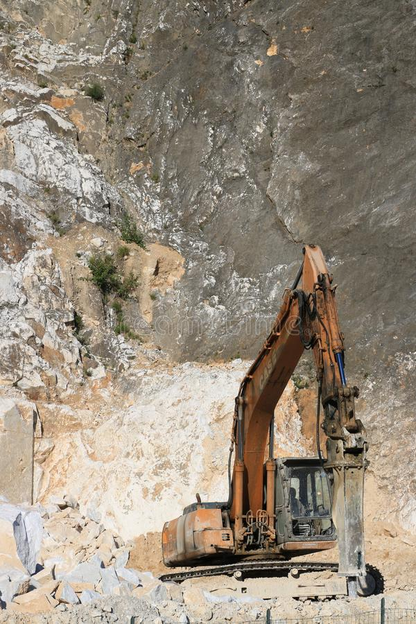 Excavator with demolition hammer in a Carrara marble quarry. A l royalty free stock photo