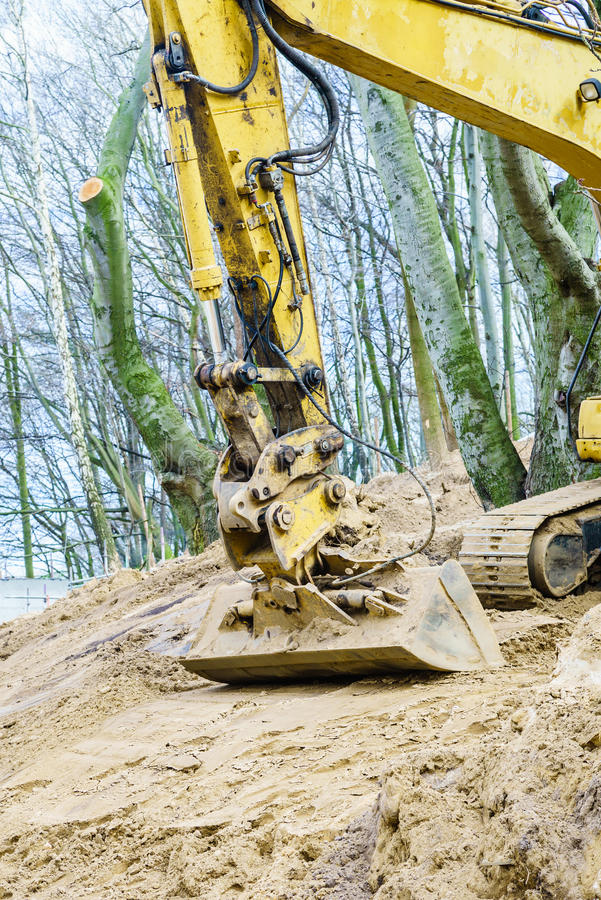 Excavator digging on site in forest environment. Yellow excavator dig digging trench on construction site in forest among trees. Devastation destruction of stock images