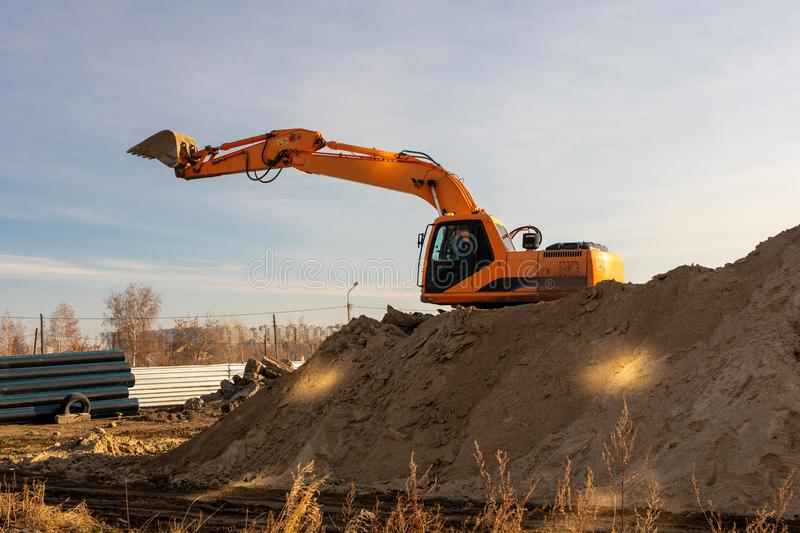 Excavator digging trench using dump truck. earthworks at construction site. heavy earth mover machine royalty free stock photos