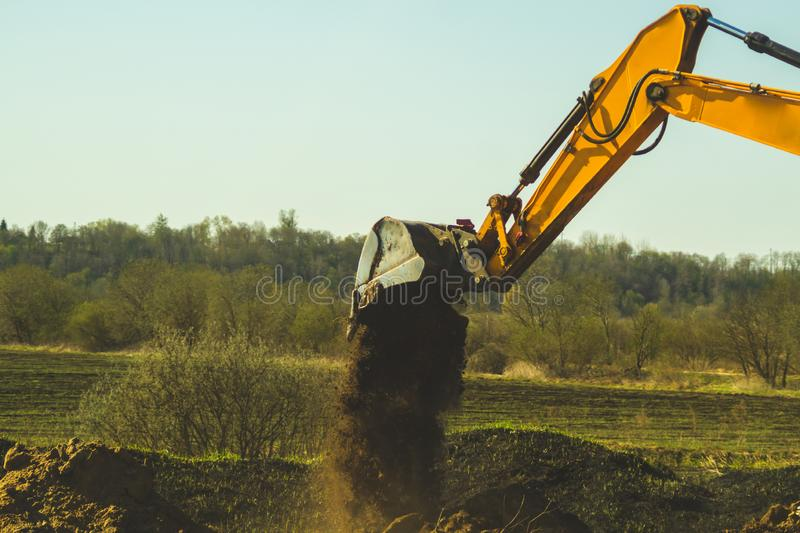 Excavator digs the ground. part of construction earthmoving equipment. digging the soil with an excavator bucket stock image