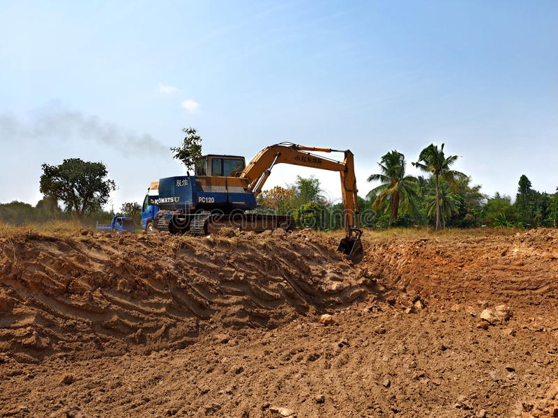 An excavator digs a pond royalty free stock photo