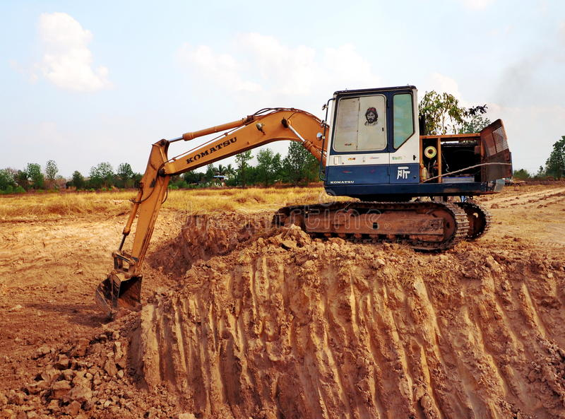 An excavator digs a pond stock images