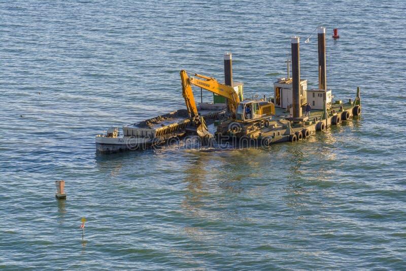 Excavator dredging on floating platform royalty free stock images