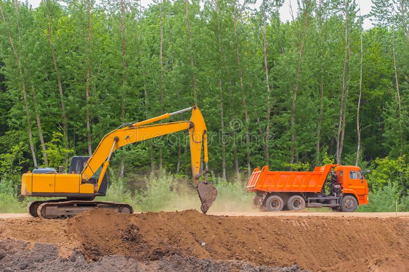Excavator and dump truck on the construction of a highway. Excavator and dump truck on the construction of a country highway stock image