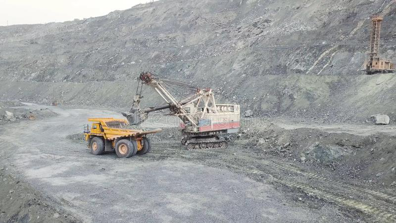 Excavator and dump truck while loading stone ore in a grey quarry, mining industry. Stock. Heavy mining excavator loads. Excavator and dump truck while loading stock photos