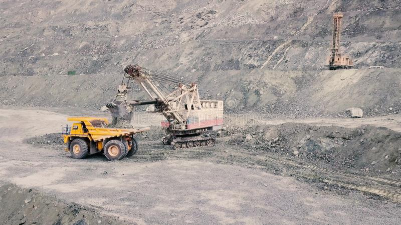 Excavator and dump truck while loading stone ore in a grey quarry, mining industry. Stock. Heavy mining excavator loads. Excavator and dump truck while loading stock images