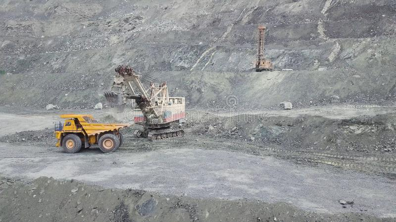 Excavator and dump truck while loading stone ore in a grey quarry, mining industry. Stock. Heavy mining excavator loads. Excavator and dump truck while loading stock photography