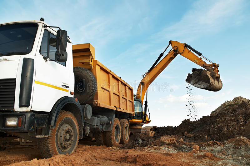 Excavator and dumper at loading royalty free stock image