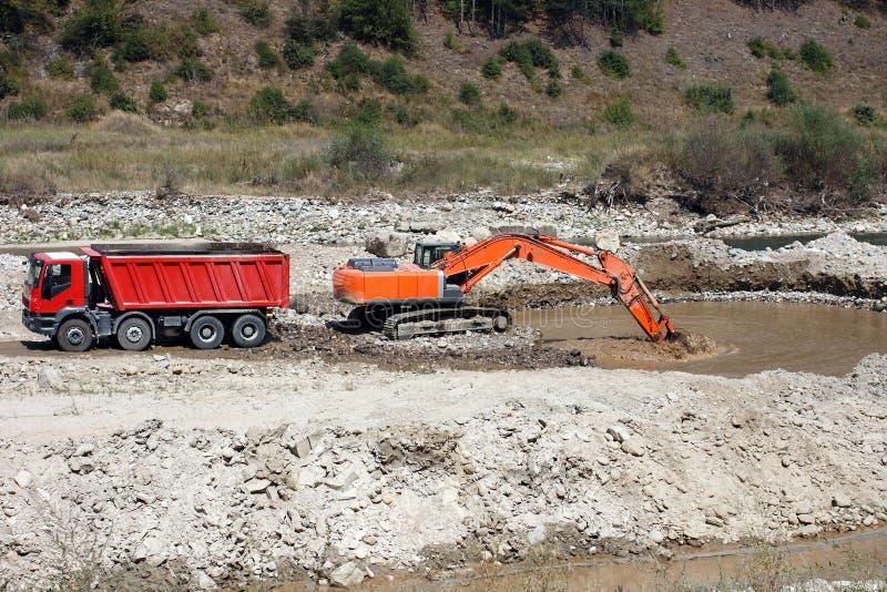 Excavator and dumper truck tipper stock photos
