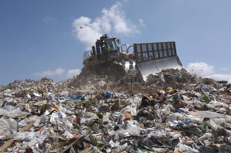 An Excavator At Dumping Ground. Against sky royalty free stock photo
