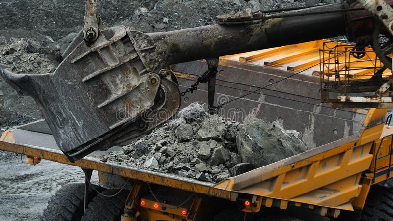 Excavator fills dump truck. Bucket excavator closeup loads stones into body of dump truck on mining or construction of. Something royalty free stock images