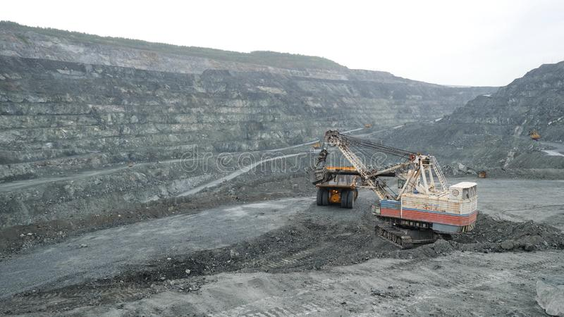 Excavator fills dump truck with earth in open pit. Heavy machinery works in mining industry in open pit.  stock photos