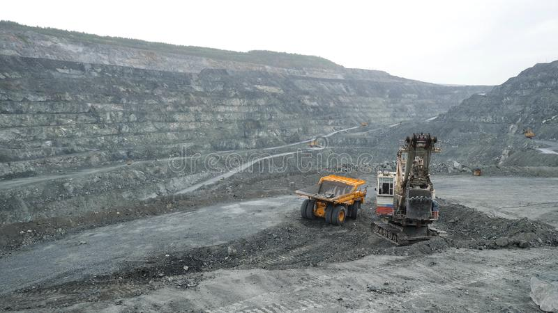Excavator fills dump truck with earth in open pit. Heavy machinery works in mining industry in open pit.  stock image