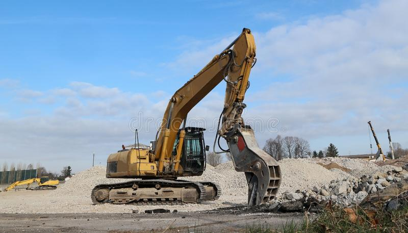 An excavator in front of a pile of  rubble  during an urban redevelopment. In the background two telescopic cranes.  royalty free stock photo