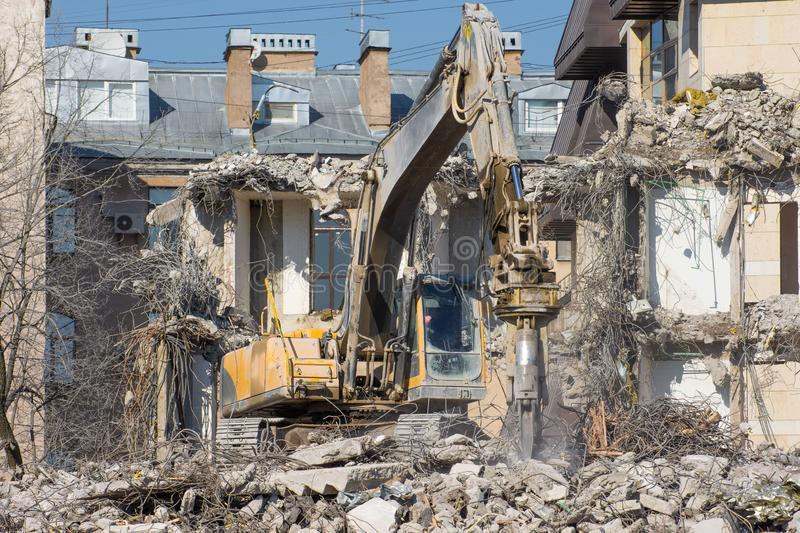 Excavator with hydraulic shears against the background of a demolished building. Dismantling of emergency construction.  stock photography
