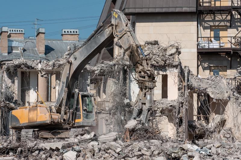 Excavator with hydraulic shears for dismantling the ruins of the house, demolition.  stock images