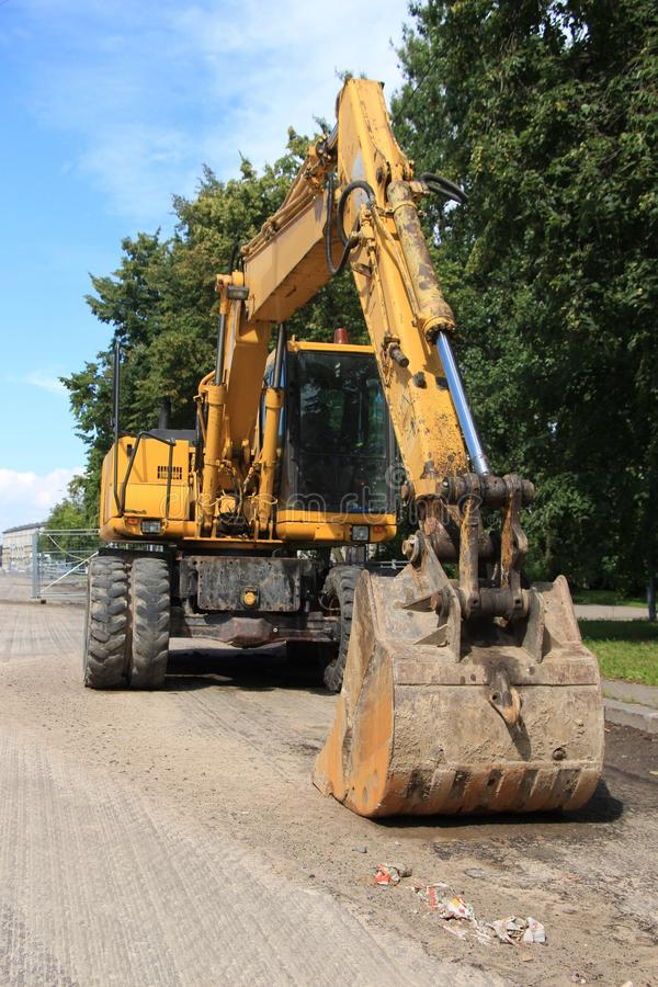 Excavator with large bucket. Yellow excavator in the street stock photography