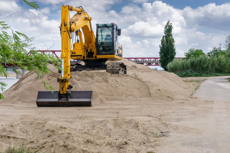 Excavator loader machine during earthmoving works outdoors at construction site stock image